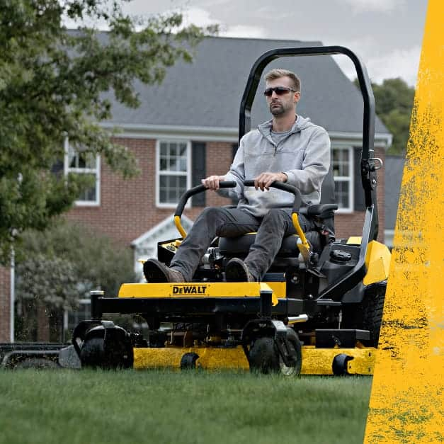 Landscaper with Dewalt zero-turn mower on trailer