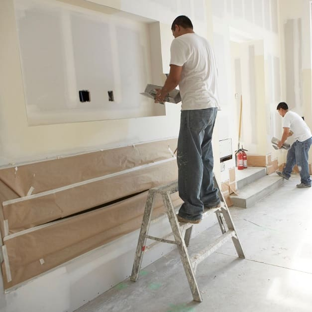 Two men putting joint compound on wallboard