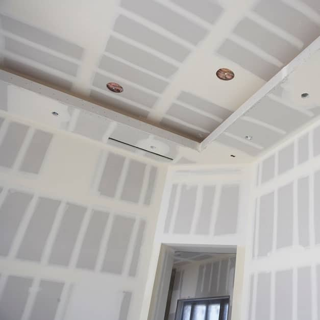 Large scene of room with wallboard finished with joint compound applied to walls and ceilings