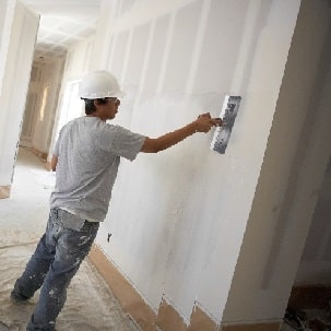 Man smoothing joint compound over wallboard with large taping knife