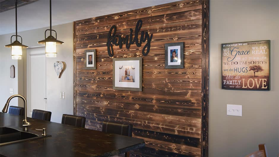 Charred wood shiplap accent wall with 3 family pictures on the wall in the family kitchen area.