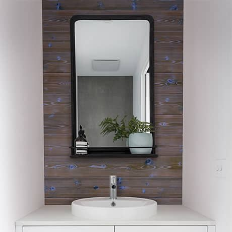 Image of a bathroom sink and mirror with a dark brown with pops of blue charred shiplap board as a accent wall