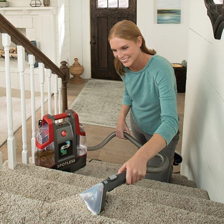 A woman using the Hoover Professional Series Portable Carpet Cleaner showing its powerful stain removal on carpeted stairs.
