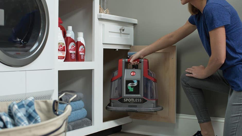 A woman storing the Hoover Professional Series Spotless Portable Carpet and Upholstery Cleaner in a laundry room cabinet showing its compact size.