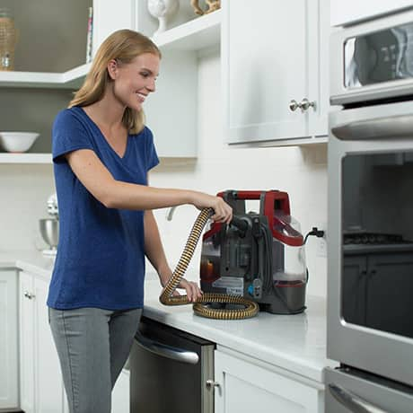 The Hoover Professional Series Spotless Portable Carpet and Upholstery Cleaner being refilled on a kitchen counter showing its self-clean technology.