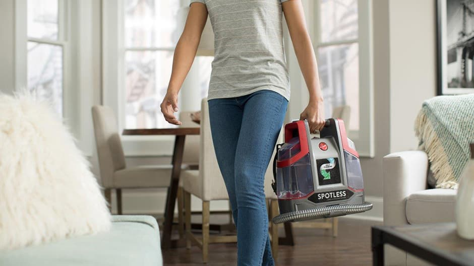 A woman carrying the Hoover Professional Series Spotless Portable Carpet and Upholstery Cleaner showing how portable and lightweight it is.