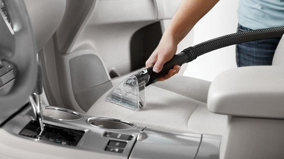 Hoover Turbo Scrub Carpet Cleaner demonstrating the upholstery tool being used on a seat in a car.