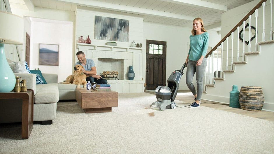 A woman using the Hoover Turbo Scrub Carpet Cleaner in a living room with a man and dog on the couch.