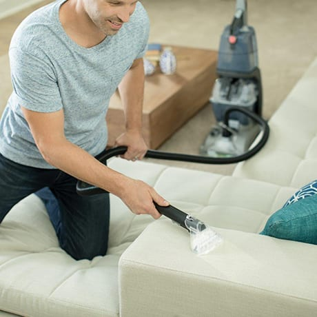 A man using the 8 foot upholstery tool of the Hoover Turbo Scrub Carpet Cleaner on a couch.