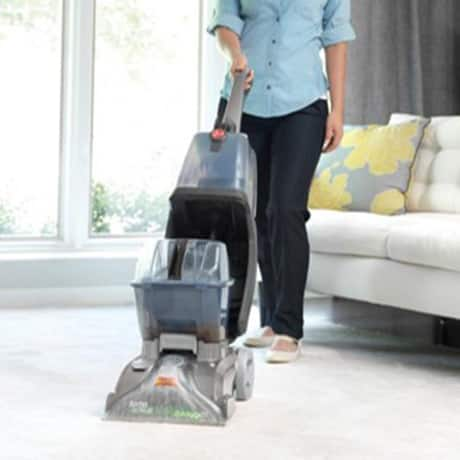 A woman using the Hoover Turbo Carpet Cleaner showing the SpinScrub 360 Technology up close in a living room setting.