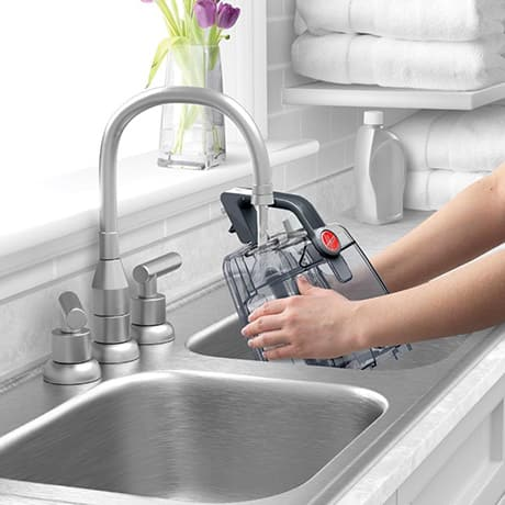 A woman filling up the water tank of the Hoover Turbo Scrub Carpet Cleaner in the sink.