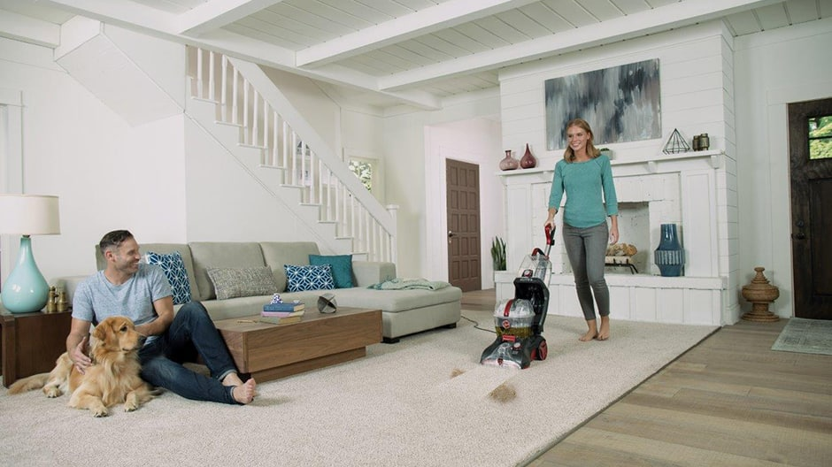 A woman using the Power Scrub Elite Pet Plus Carpet Cleaner in a living room with a man and dog sitting near the couch.