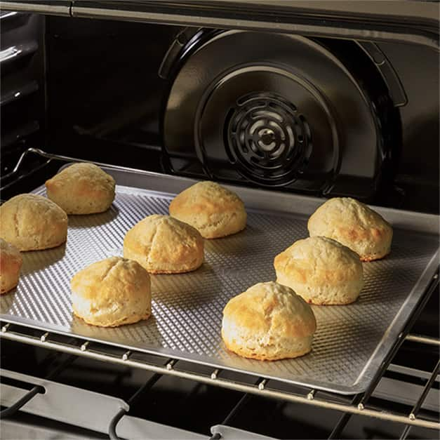 Biscuits sitting on a baking sheet in the oven with the convection fan in the back