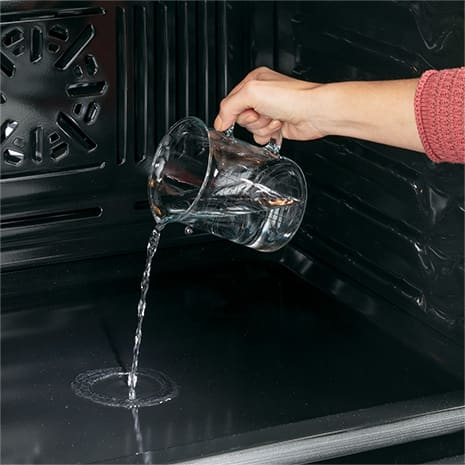 Image of hand pouring water on the bottom of the oven cavity for steam clean