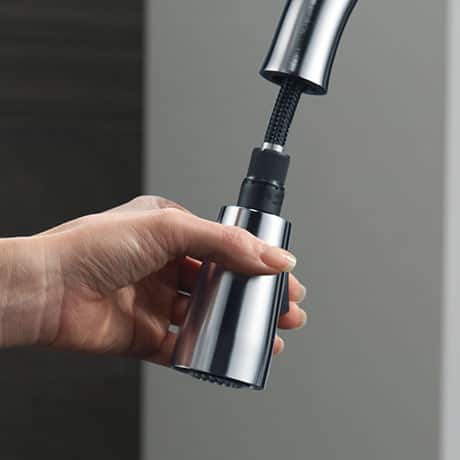 Image depicts an up-close view of the base of a pull-down faucet spout being pulled out by a hand model