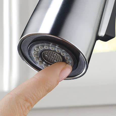 Image depicts a finger wiping away build-up from the bottom of a faucet spout