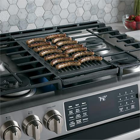 Image of food cooking on the grill on the cooktop of range