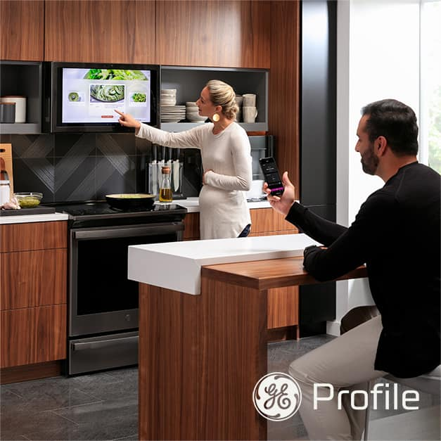 A man monitors appliance settings on his phone while a woman in the background interacts with the kitchen hub in their high-tech kitchen
