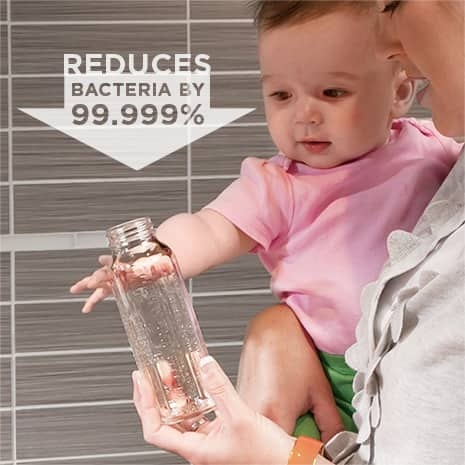 Image of baby reaching for baby bottle and text overlay that shows that steam + sani reduces 99.999% of bacteria
