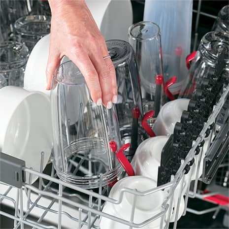 Shot of woman's hand placing a bottle on the bottle jet inside the dishwasher