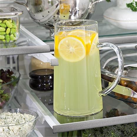 Large pitcher of lemonade on shelf, with top shelf pushed back