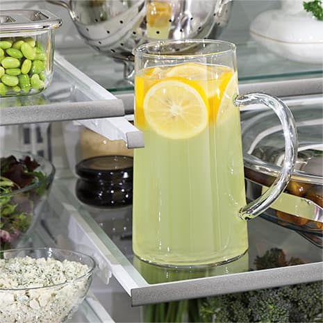 The upper shelf has been moved out of the way to make room for a tall pitcher of lemonade.