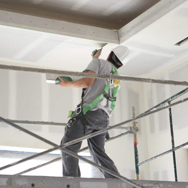 Man on scaffolding applying joint compound to wallboard ceiling