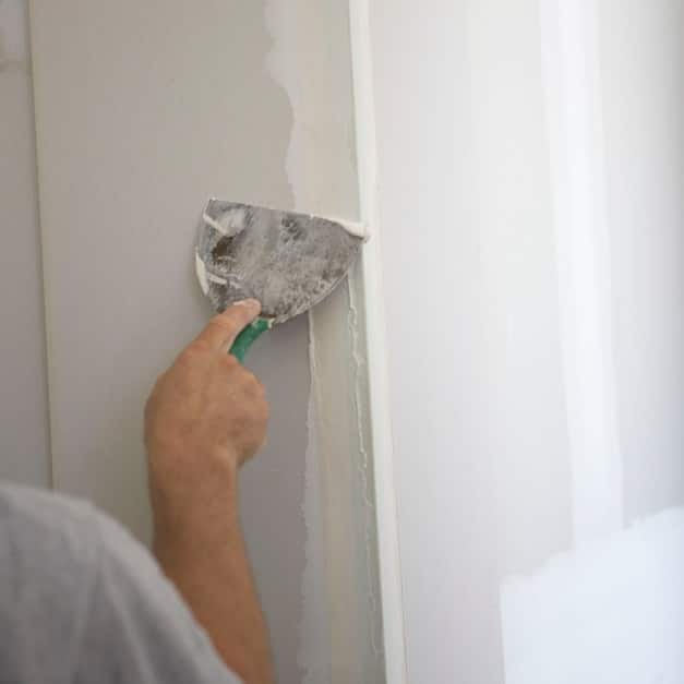 Close up of hand applying joint compound to wall with a taping knife