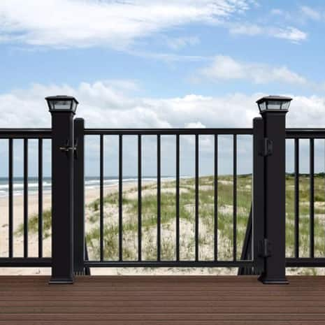 A view looking outward to a beach featuring the deck gate installed on a composite deck