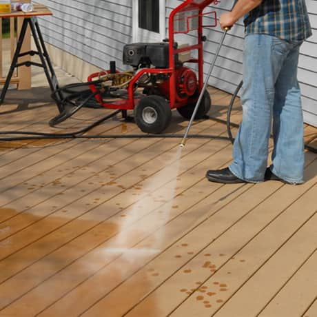 A sunny day of a man using a powerwasher to clean his deck boards