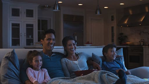 Family watching tv in the living room under dim lighting