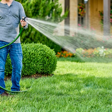 Exterior shot of person watering lawn with spray hose