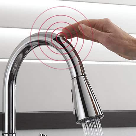 Hand touches faucet on