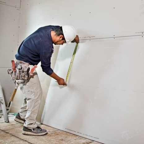 Man with measuring wallboard with tape measure
