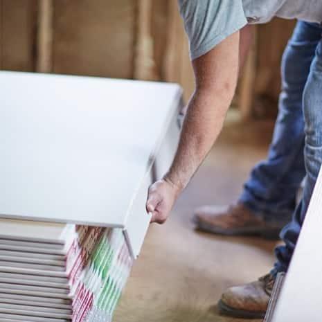 Man breaking wallboard panel at score line