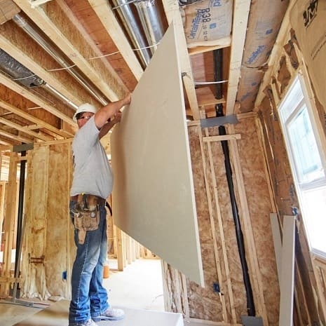Man lifting wallboard up in front of him to install on wood framing