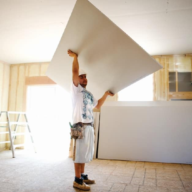 Man lifting large piece of wallboard over his head
