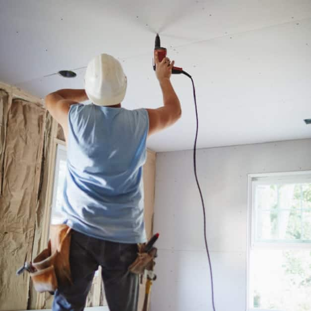 Man drilling wallboard ceiling panel into place