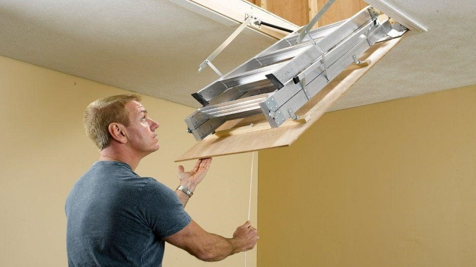Man folding the ladder into the attic