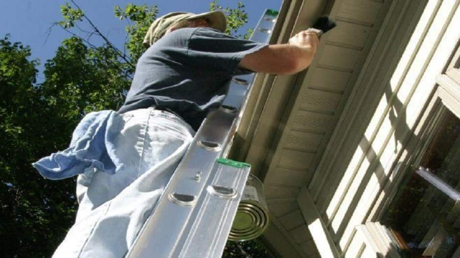 Man painting trim on extension ladder