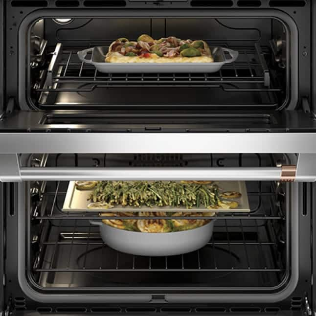 Both doors on the double oven are open.Each rack holds a different cooked food.