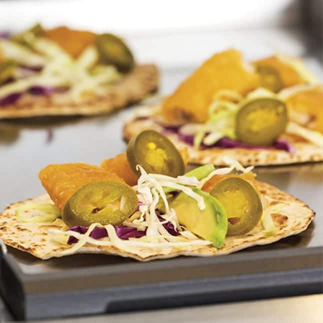 Three fully dressed tostadas are cooked on the solid griddle.