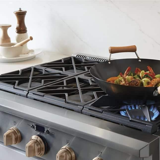 One of the burner grates on the stove has been flipped, and now holds a wok cooking Asian food.