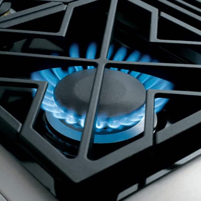 A closeup of one of the professional quality burners.Even blue flames rise from the burner, heating up the grates.