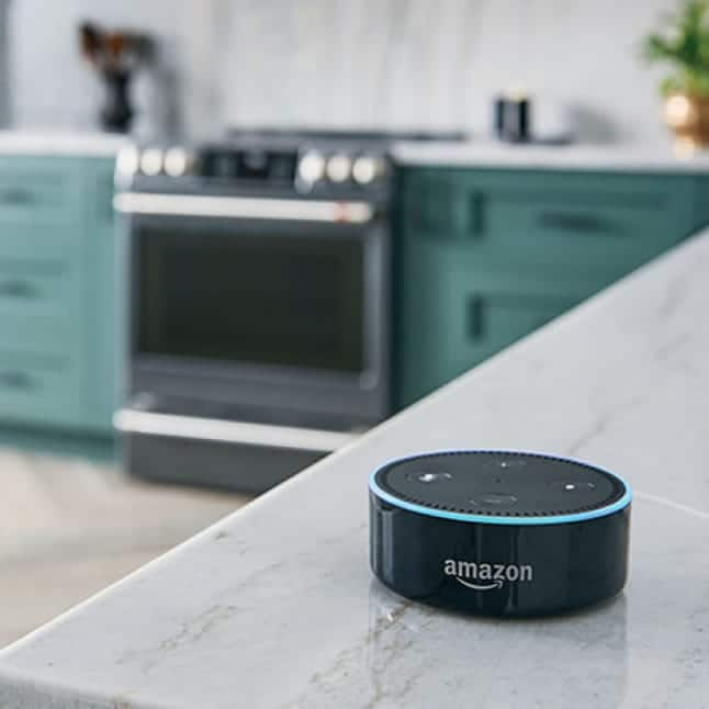 An Amazon Alexa device sits on a marble counter waiting for smart home voice commands