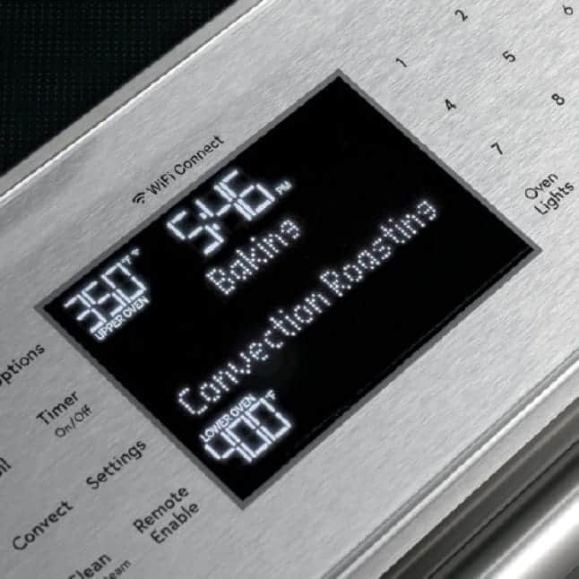 Angled image of Modern Glass electric range with a tight crop on backlit control panel