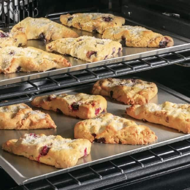 Tight image of scones cooking in the oven on baking sheets