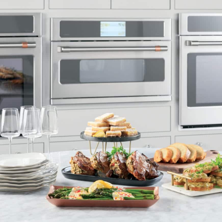 An advantium oven is installed between two wall ovens. A variety of gourmet foods are arranged on a counter in front of the ovens.