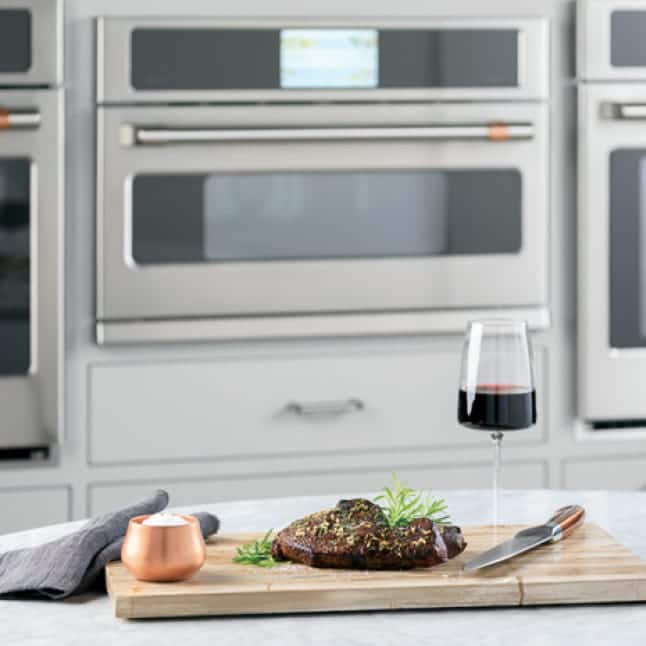 An adaptable advantium oven is installed between two larger wall ovens. A meal on a wooden tray is arranged on a counter in front of the oven.