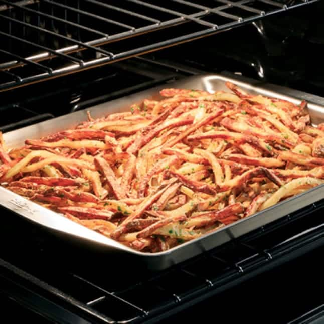 Seasoned fries in a metal tray are cooked to a crispy golden brown in a Cafe stove.